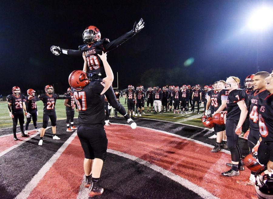 Glenbard East's Jason Torrevillas is lifted by teammate Dylan Marin after the Rams win against Prospect in a playoff football game in Lombard last season.