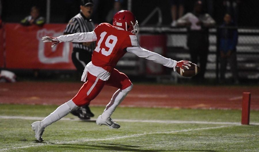 Naperville Central's Samuel Jackson crosses the goal line with a touchdown against Naperville North in a football game last season at Central High School.