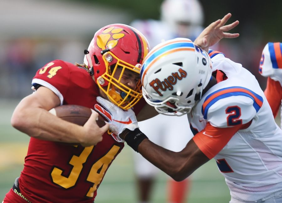 Batavia's Quinn Urwiler is hit by East St. Louis' Antonio Johnson on a carry during Saturday's game in Batavia.