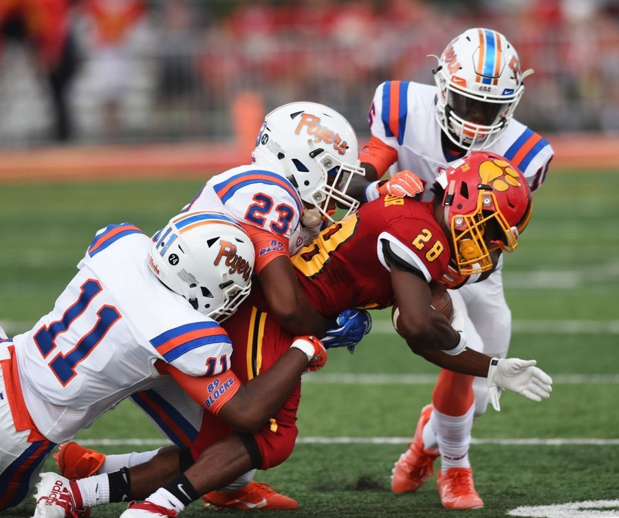 Batavia's Art Taylor is tackled by, from left, East St. Louis' Jalen Byrd, Cameron Lovett and Lamar Box Jr. during Saturday's game in Batavia.