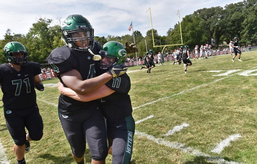 Glenbard West's Joey Richmond is picked up by teammate Braden Spiech after a long touchdown run in the first quarter against Maine South in a football game in Glen Ellyn Saturday, August 31, 2019.