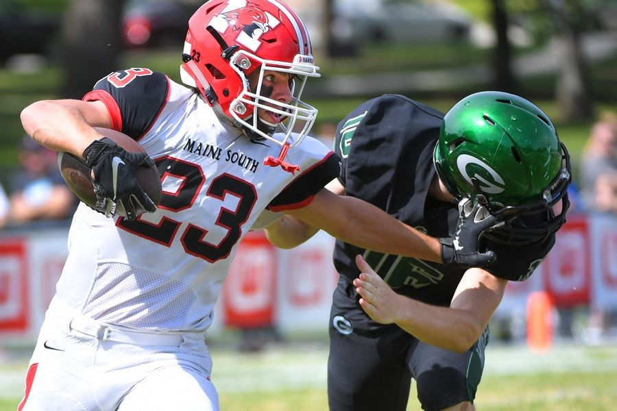 Maine South's Daniel Lazic grabs the facemark of Glenbard West tackler Patrick Devereaux in a football game in Glen Ellyn Saturday, August 31, 2019.