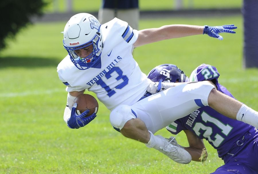 Vernon Hills' Giovanni Zullo finds his way into the end zone for a touchdown despite pressure from Waukegan's Bryan Figueroa in the first quarter of the varsity football matchup in Waukegan on Saturday.