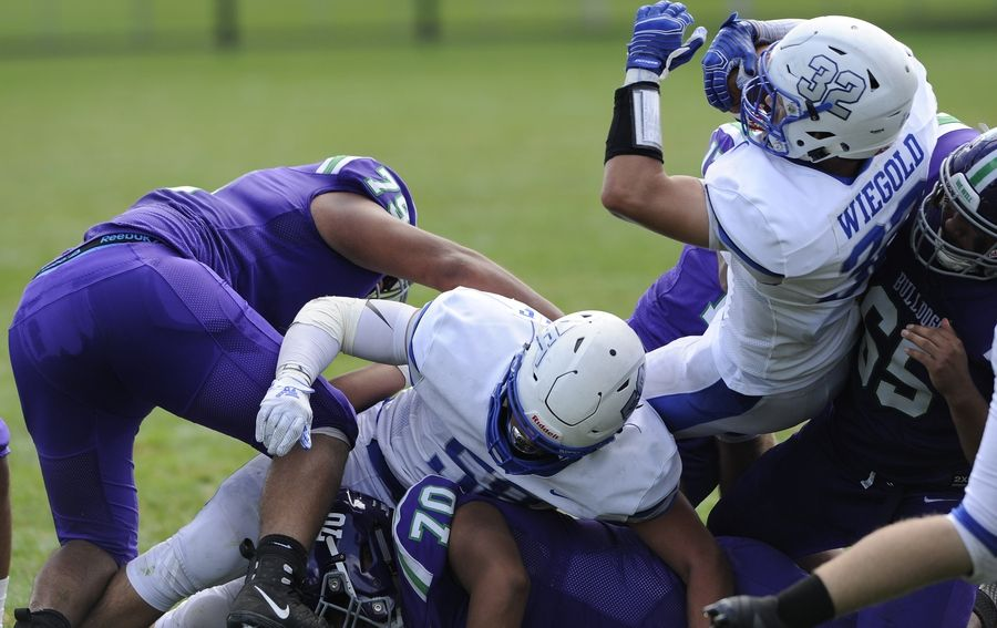 Vernon Hills' Jackson Weigold (right) plows his way through Waukegan's defense for a second-quarter touchdown in the varsity football matchup in Waukegan on Saturday.