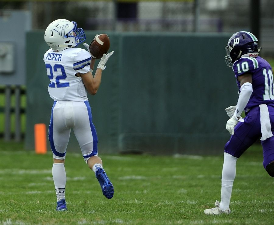 Vernon Hills' Jake Pieper hauls in a touchdown pass on the second play of the game as Waukegan's Quinton Idleburg fails to catch him in the varsity football matchup in Waukegan on Saturday.