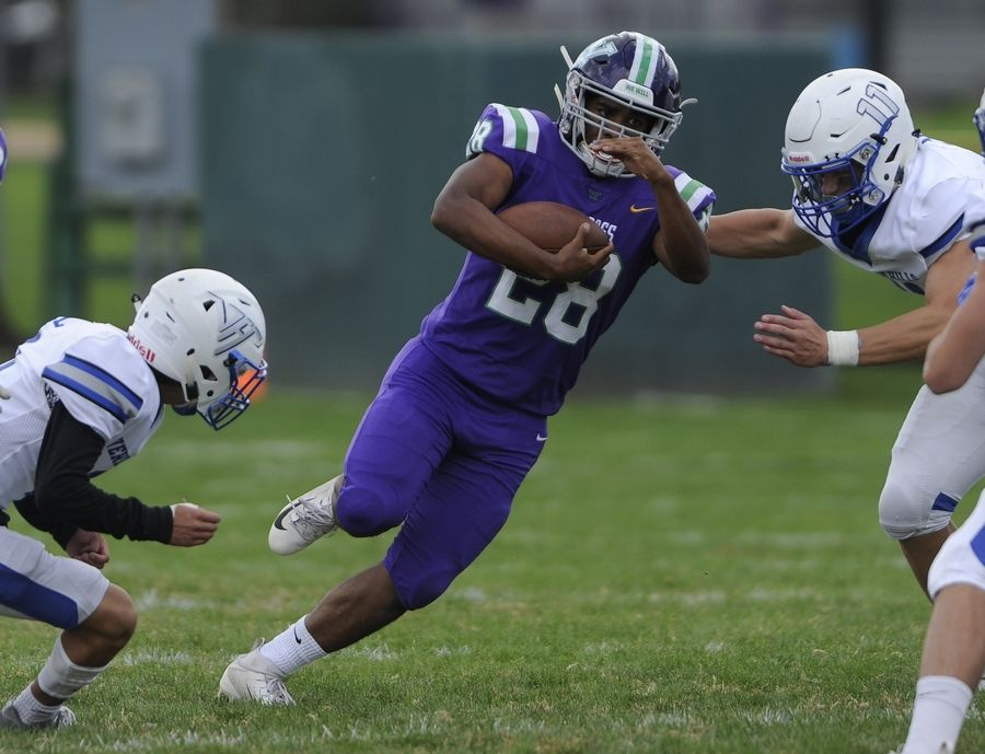 Waukegan's Angel Henry is hit high by Vernon Hills' Ryan Mann as his teammate hits him low in the first quarter of the varsity football matchup in Waukegan on Saturday.