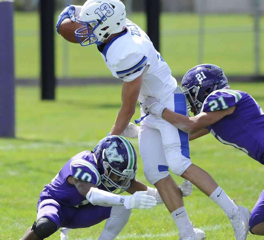 Vernon Hills' Giovanni Zullo finds his way into the end zone for a touchdown despite pressure from Waukegan's Bryan Figueroa and Quinton Idleburg in the first quarter of the varsity football matchup in Waukegan on Saturday.