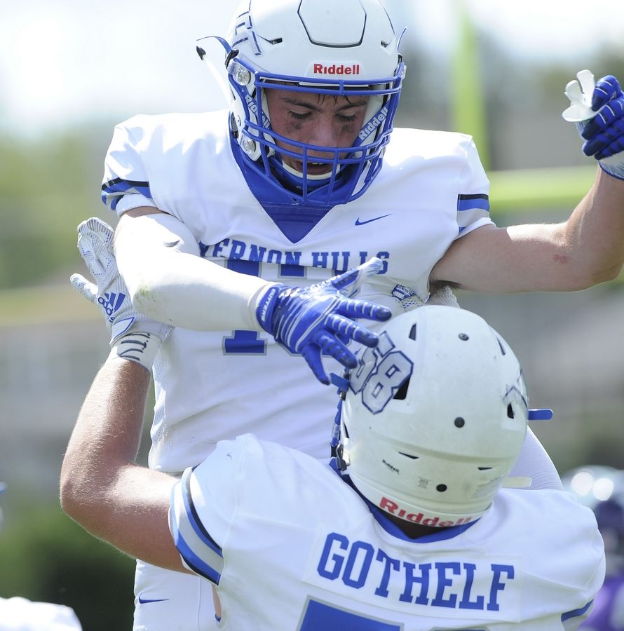 Vernon Hills' Giovanni Zullo finds his way into the end zone for a touchdown and celebrates with his teammate Bradley Gothelf in the varsity football matchup in Waukegan on Saturday.