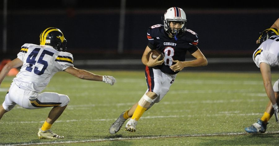 Conant quarterback Gluseppe Dugo gains yardage during the first quarter in the varsity matchup against Glenbrook South at Conant on Friday.