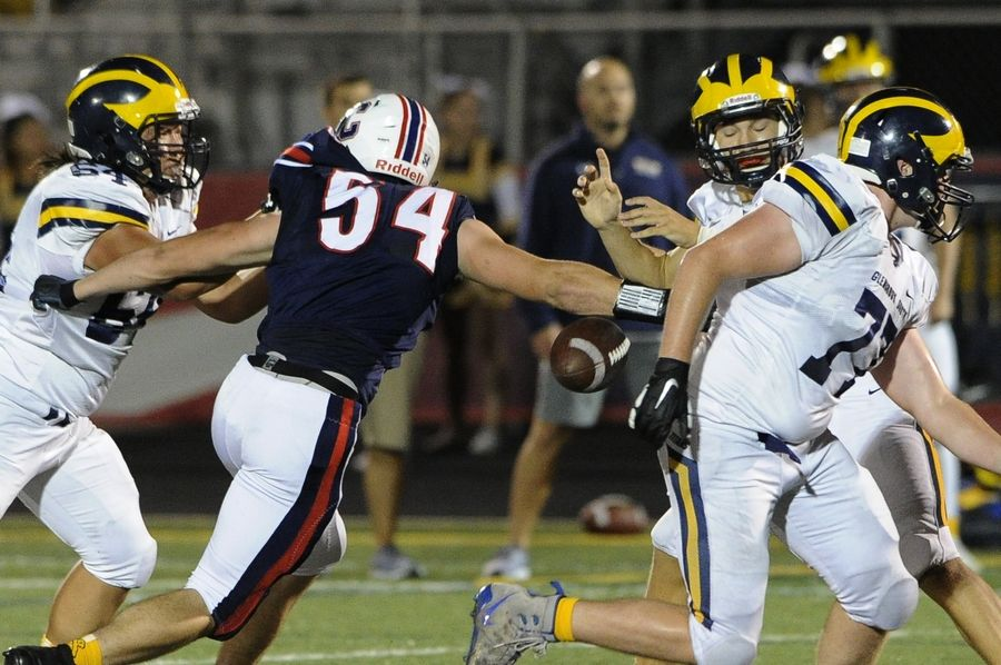 Conant's Derek Lewandowski knocks the ball away from Glenbrook South's quarterback Michael Bauer in the second quarter and the ball is recovered by Conant in the varsity matchup against Glenbrook South at Conant on Friday.