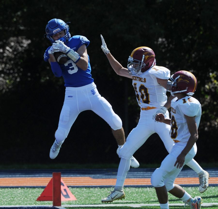 St. Francis football player Jake Tangorra makes a leaping catch for a touchdown despite pressure from Westmont's defense in the first quarter of the varsity football matchup held at Wheaton College McCully Stadium on Saturday.