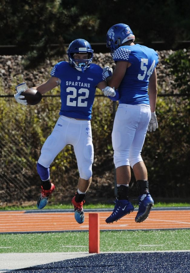 St. Francis football player Ben Radel and teammate TJ McMillen celebrate Radel's touchdown in the first quarter in the varsity football matchup held at Wheaton College McCully Stadium on Saturday.