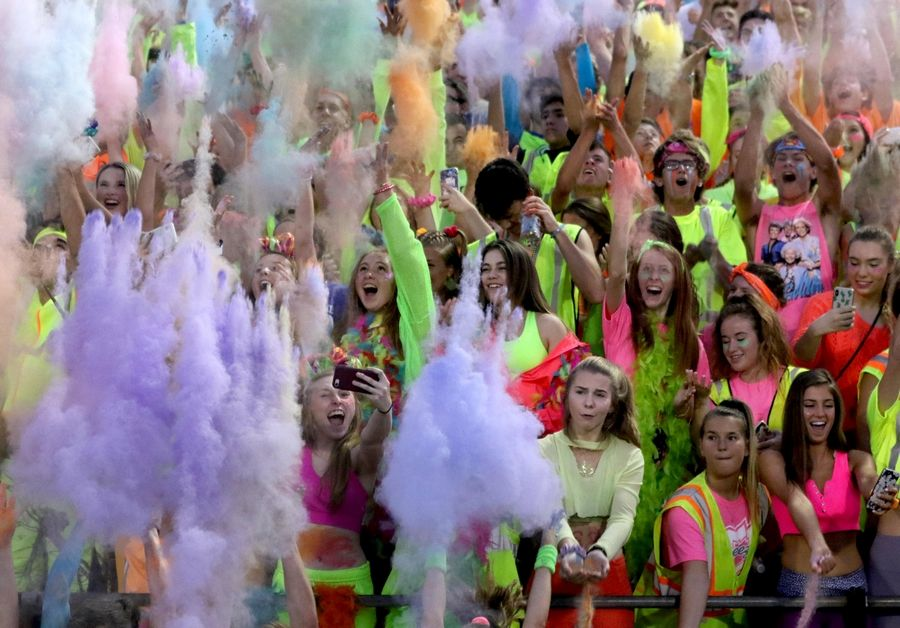 Cary-Grove fans toss colorful dust for the kickoff against Huntley in varsity football at Al Bohrer Field on the campus of Cary-Grove High School Friday night.