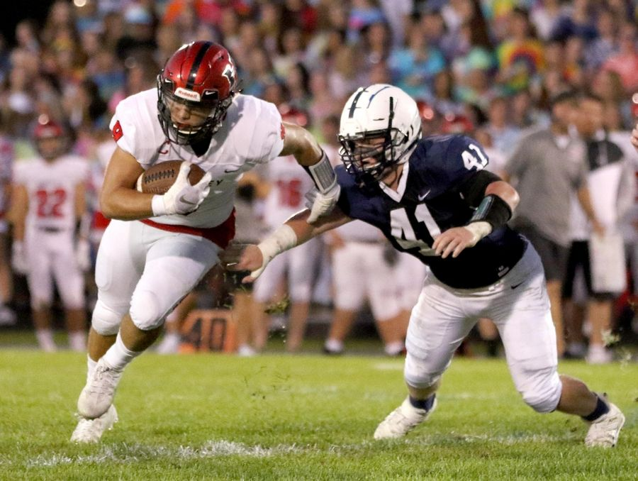 Cary-Grove's Jake Johnson, right, pursues Huntley's Ricciardi Pasquale in varsity football at Al Bohrer Field on the campus of Cary-Grove High School Friday night.
