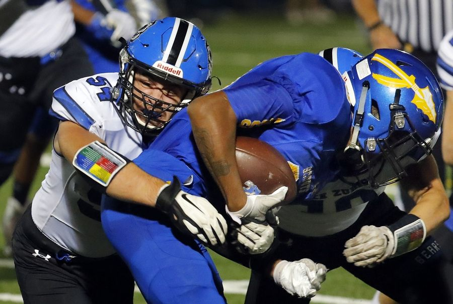 Lake Zurich's Joey Shahwan, left, tackles Lake Forest's Jahari Scott during their game Friday night at Lake Forest High School.