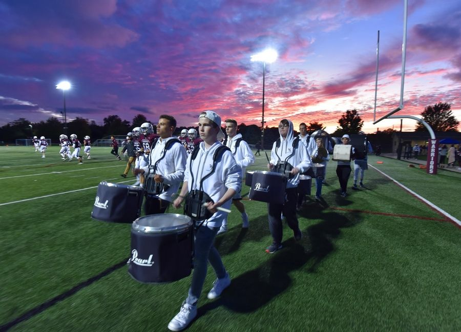 The Wheaton Academy marching band percussion section makes an entrance to the field before a football game against Bishop McNamara in West Chicago Thursday.