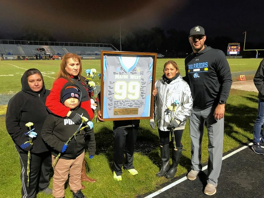 The family of former Maine West football player Arturo Quintero, who was honored on Senior Night last week displays a framed jersey of Quintero's. He was a freshman on the football team at Maine West and he would have been a senior this year. He was killed, along with his father and one of his brothers, after his freshman year in a car accident. At far right is Maine West coach Jason Kradman.