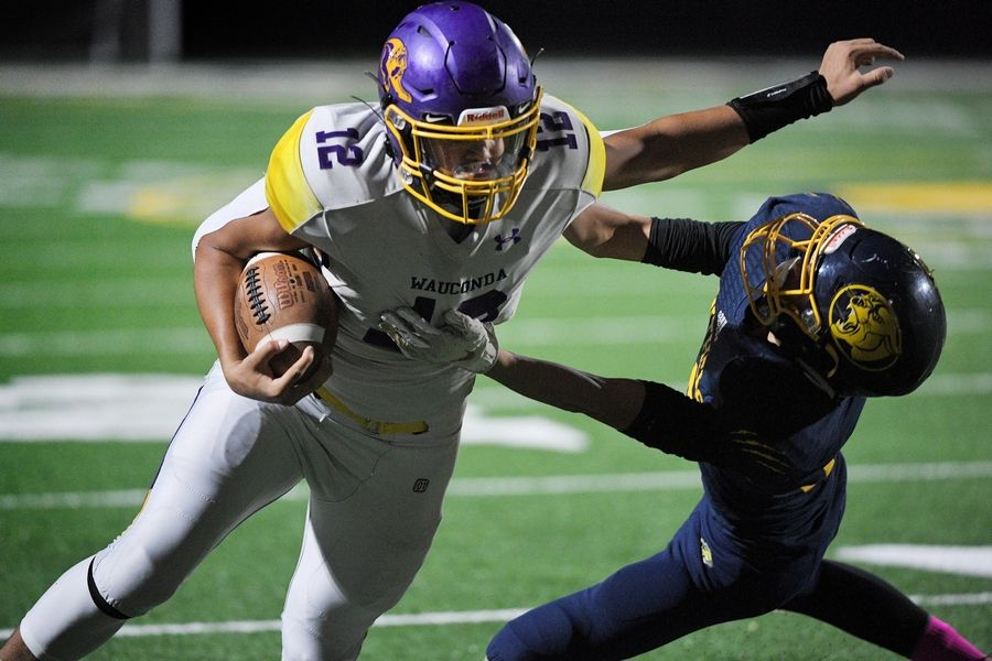 Wauconda's JJ Jacobo stiff arms Round Lake's Shawn Rios as he runs for a touchdown in a football game in the new Round Lake High School stadium in Round Lake Friday.
