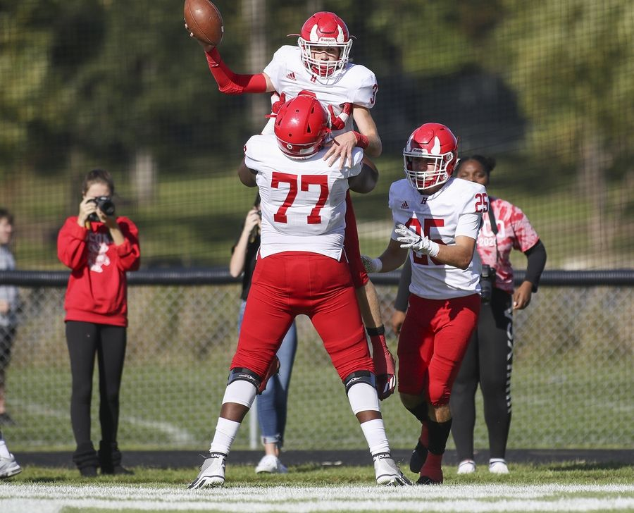 Hinsdale Central's Mark Skokna (3) is hoisted up by Kiran Amegadjie (77) after scoring a touchdown against Glenbard West in Glen Ellyn Oct. 19.