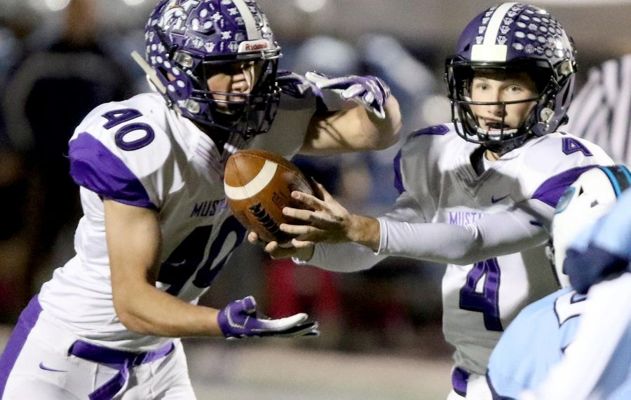 Rolling Meadows' Chris Divito, left, grabs the ball from quarterback Carson Schiller against Prospect earlier this season. Meadows travels to Hersey Friday night with the Mid-Suburban East title on the line.