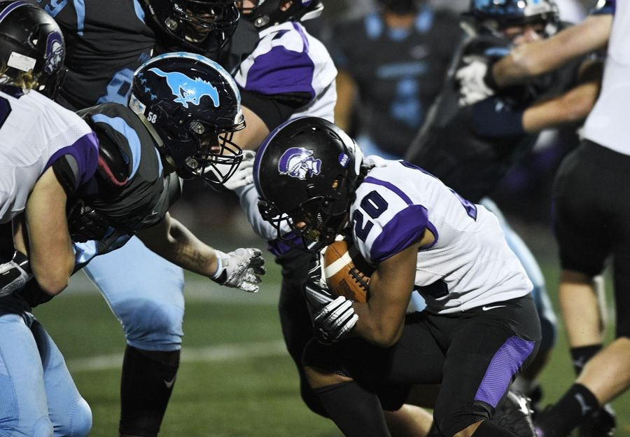 Downers Grove North's Joshua Lumpkin carries the ball as Downers Grove South's Nathan Gustafson moves in for the tackle during Friday's game.