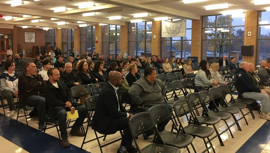 A large crowd Lake Park High School parents and graduates attended a school board meeting Wednesday to voice their support for the Roselle school's head coach, Chris Roll, who was suspended last week.
