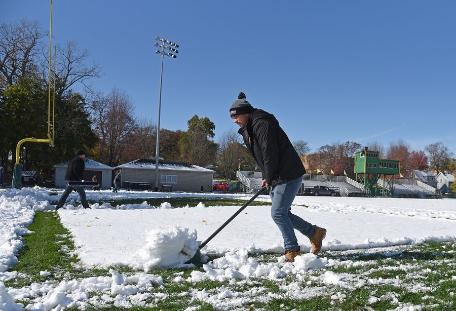 Kyle Tourtellott of Elgin, a 2008 graduate and former football player, was among several volunteers who cleared the snow from the St. Edward Central Catholic High School football field Friday afternoon in Elgin.