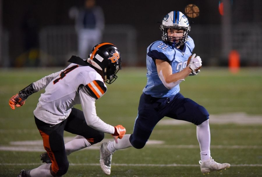 Prospect's Noah Marx runs in the first quarter against DeKalb's Bilal Hobbs in a first round Class 7A playoff football game Friday in Mount Prospect.