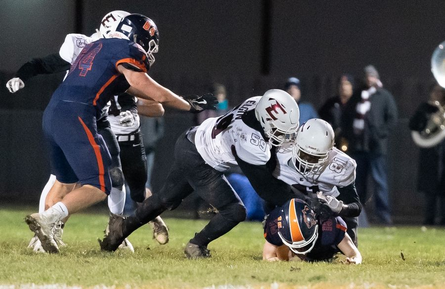 Elgin's Shannon Williams (59) and Ja'Kare Watson (81) tackle Oswego's Cole Pradel (15) during a 8A playoff game at Oswego High School in Oswego, IL on Friday, November 01, 2019