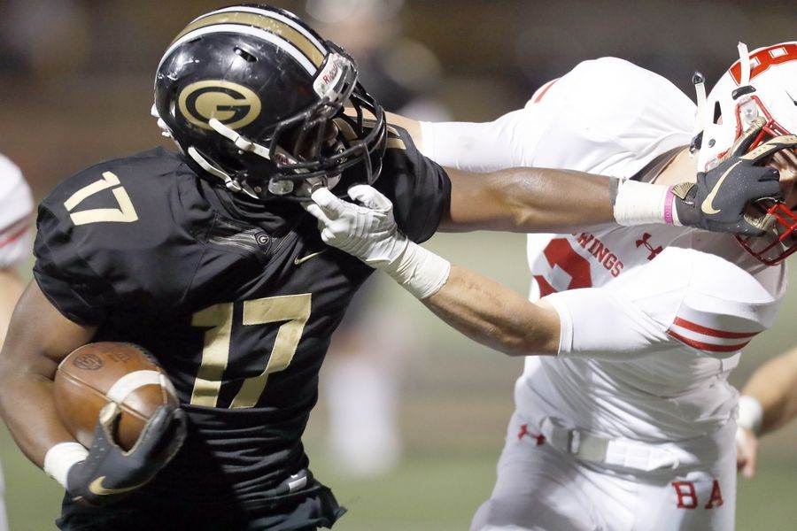 Glenbard North's Jordan McQuarter (17) battles Benet's Tommy O'Malley (2) Friday during the first-round Class 7A football playoff in Carol Stream.