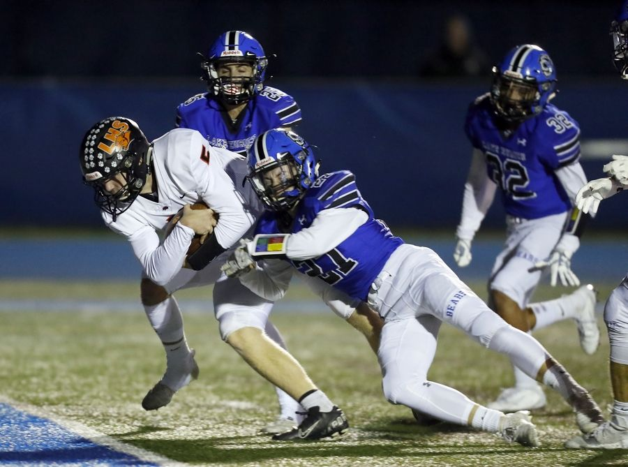 Libertyville's Blake Ellingson (5) muscles his way in for a touchdown past Lake Zurich's Kyle Forbes (27) and Anthony Mangano (25) Friday during Week 6 action in Lake Zurich.