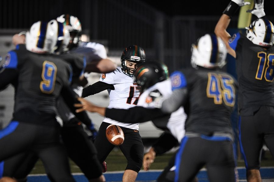 Plainfield East's Ahmad Elshalakany (17) attempts to punt during the first quarter, but the ball was blocked by Warren's Juan DelaCruz (18), who recovered the ball in the end zone for a touchdown during the Class 8A football playoffs in Gurnee Saturday.