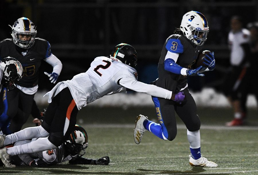 Warren's Derrick McLaughlin carries the ball up the middle of the field as he is tackled by Plainfield East's Brian Tape during the Class 8A football playoffs in Gurnee Saturday.