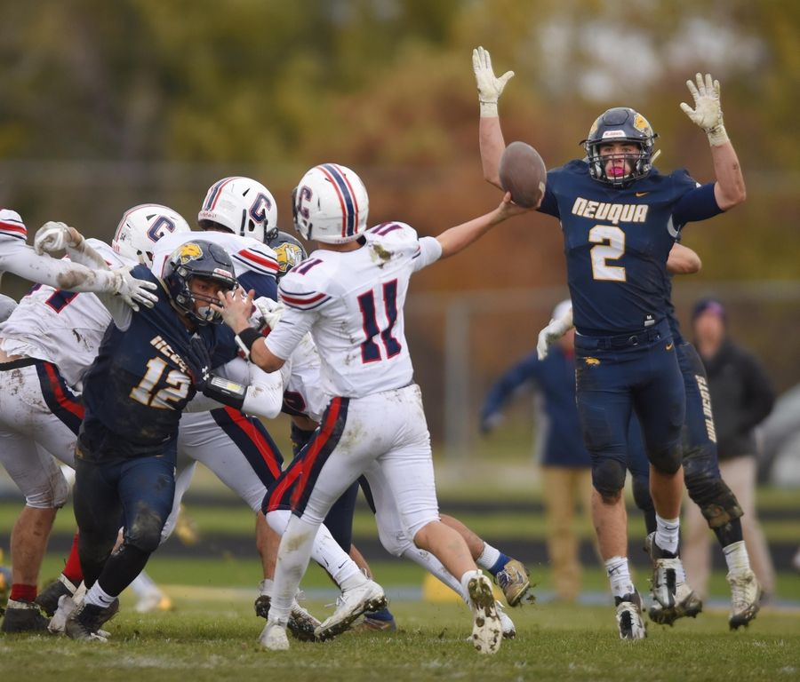 Neuqua Valley's Jack Belskis tries to block a pass by Conant's Matthew Botello in a first-round playoff football game in Naperville Saturday.