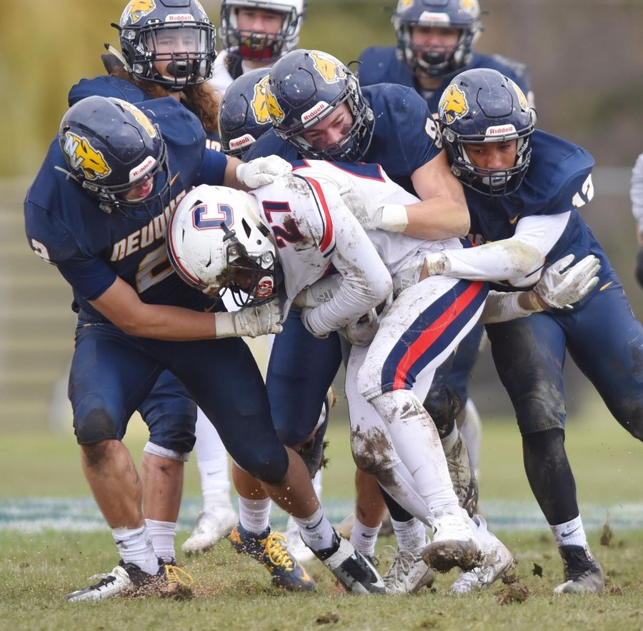 Conant's Malik Frederick is gang-tackled by Neuqua Valley's Jack Belskis, Nathan Williamson and Emanuel Rice in a first-round playoff football game in Naperville Saturday.