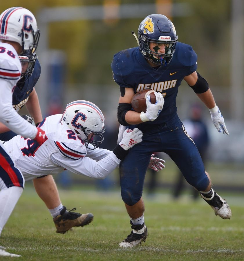 Neuqua Valley's Nick Pastore tries to escape Conant's Jeremy Betancourt in a first-round playoff football game in Naperville Saturday.