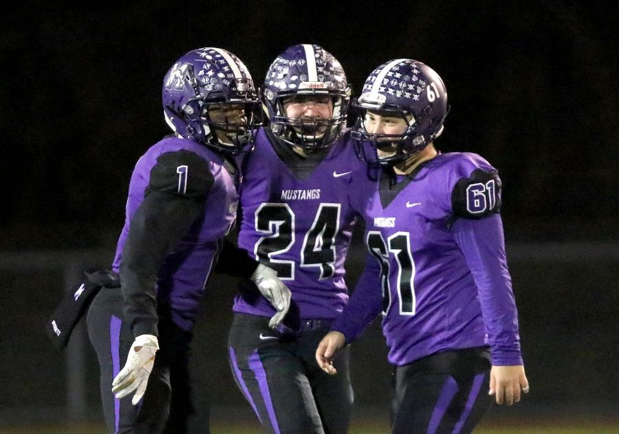 From left, Rolling Meadows' Nife Oseni, Sean Nolan, and Brian Sroka are all smiles during playoff football at Robert A. Hoese Field on the campus of Rolling Meadows High School Friday night.