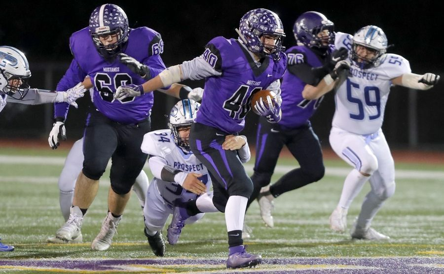 Rolling Meadows' Chris Divito runs the ball during playoff football at Robert A. Hoese Field on the campus of Rolling Meadows High School Friday night.