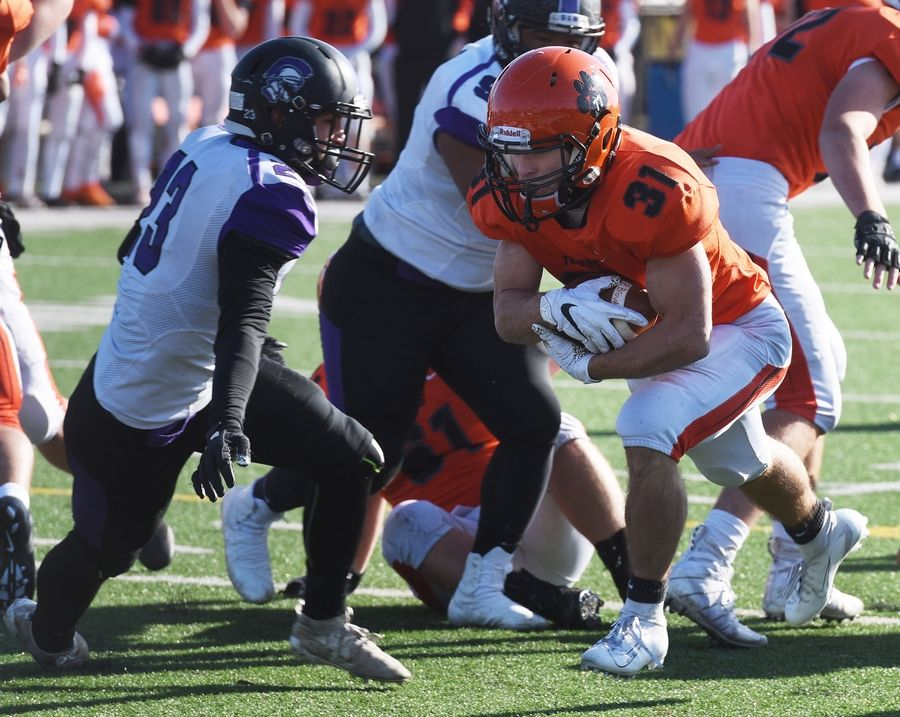 Wheaton Warrenville South's Jake Arthurs powers his way to the goal line for a touchdown as Downers Grove North's  Ryan Schindler closes in during Saturday's game in Wheaton.