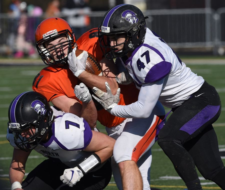 Wheaton Warrenville South's Jason Haw gets tackled by Downers Grove North's Drew Cassens, left, and Jon Werthman during Saturday's game in Wheaton.