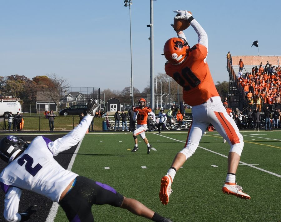 Wheaton Warrenville South's Danny Healy makes an interception in front of Downers Grove North's Kevin Bozeman during Saturday's game in Wheaton.