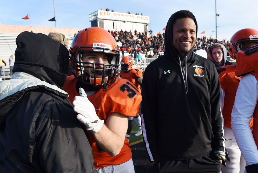Wheaton Warrenville South's Jake Arthurs hugs strength and conditioning coach Jack Van Diver along the sidleine after his fourth-quarter touchdown against Downers Grove North made the score 28-7 during Saturday's game in Wheaton.