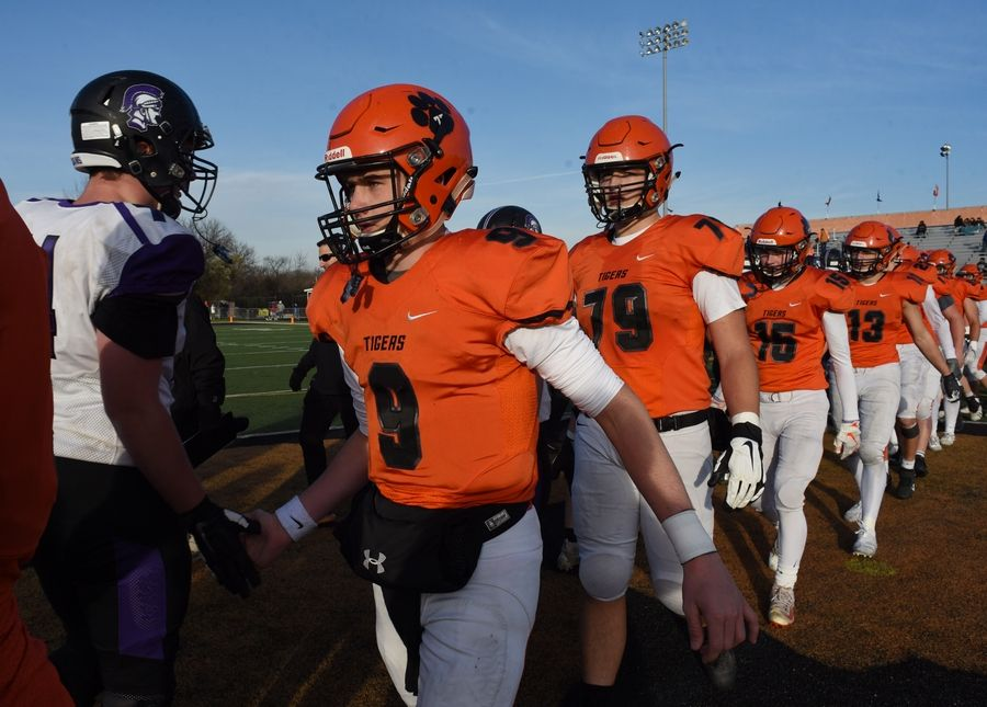 Wheaton Warrenville South quarterback Parker Brown shakes hands with Downers Grove North players following his team's 28-7 vicotry during Saturday's game in Wheaton.