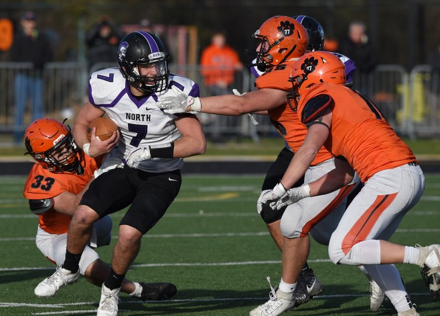 The Wheaton Warrenville South defense including, left to right, Micah Roberts, Ben Burger and Michael Rogers closes in on Downers Grove North quarterback Drew Cassens as he rushes for yardage during Saturday's game in Wheaton.