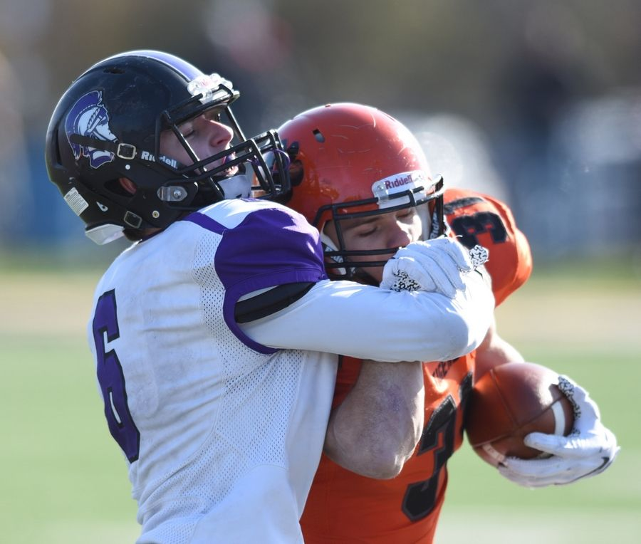 Downers Grove North's Henry Gates wraps his arms around Wheaton Warrenville South ball carrier Jake Arthur and pushes him toward the sideline during Saturday's game in Wheaton.
