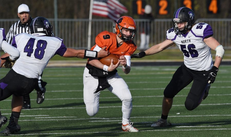 Wheaton Warrenville South quarterback Parker Brown runs between Downers Grove North's Drew Bielawski (48) and Seth Peterson during Saturday's game.
