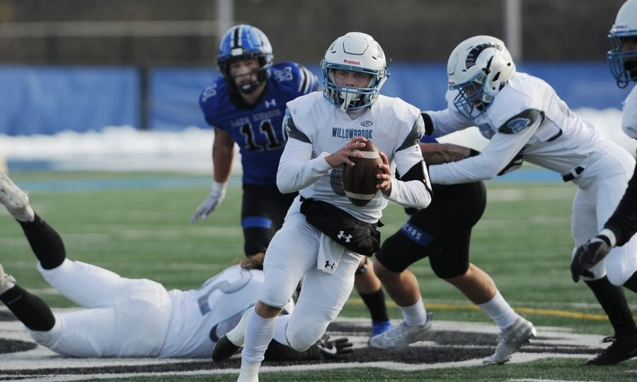 Willowbrook quarterback Sam Tumilty scrambles for yardage away from Lake Zurich's defense in the Class 7A football playoffs at Lake Zurich on Saturday.