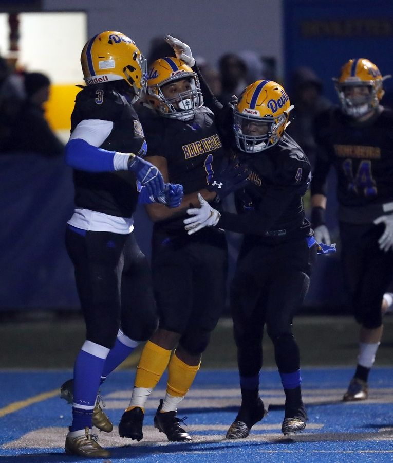 Warren's Christian Phillips (1) is greeted by his teammates after his touchdown Saturday during the IHSA Class 8A state semifinals in Gurnee.