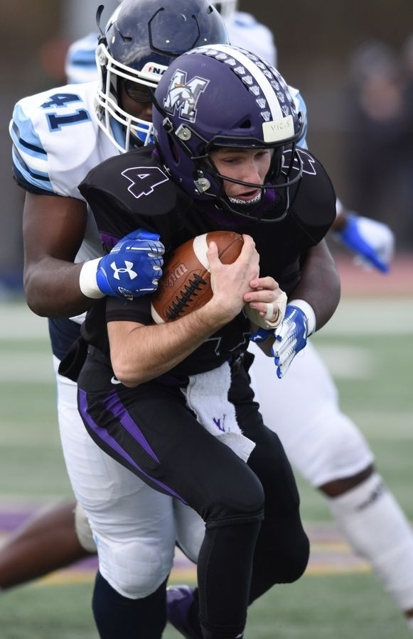 Rolling Meadows quarterback Carson Schiller gets tackled by Nazareth's Amarion Evans during the Class 7A state football semifinal in Rolling Meadows Saturday.
