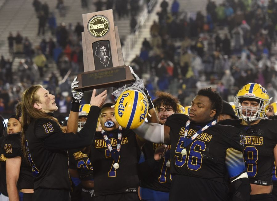 Warren players including Adam Saul (19), Josh Turner (7) and Willis Singleton (56) hold their team's second-place trophy following their 12-0 loss to Lincoln-Way East during the IHSA Class 8A state football championship game at Northern Illinois University in DeKalb Saturday.
